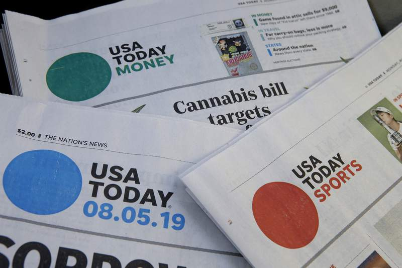 FILE - In this Aug. 5, 2019, file photo, sections of a USA Today newspapers in Norwood, Mass. The FBI issued a subpoena demanding U.S. newspaper giant Gannett provide agents with information to track down readers of a USA Today story about a suspect in a child pornography case who fatally shot two FBI agents in February.  (AP Photo/Steven Senne, File)