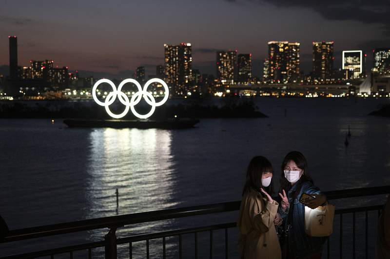 """Two women take a selfie with the Olympic rings in the background in the Odaiba section of Tokyo, Thursday, March 12, 2020. Tokyo Governor Yuriko Koike spoke Thursday after the World Health Organization labeled the spreading virus a """"pandemic,"""" a decision almost certain to affect the Tokyo Olympics. (AP Photo/Jae C. Hong)"""