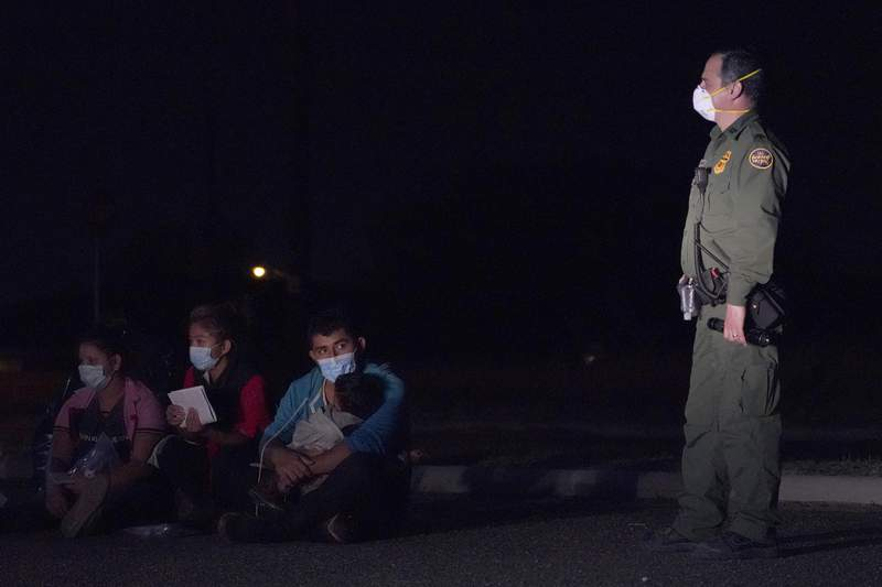 A migrant man, center, holds a child as he looks at a U.S. Customs and Border Protection agent at an intake area after crossing the U.S.-Mexico border, early Wednesday, March 24, 2021, in Roma, Texas. A surge of migrants on the Southwest border has the Biden administration on the defensive. The head of Homeland Security acknowledged the severity of the problem but insisted it's under control and said he won't revive a Trump-era practice of immediately expelling teens and children. (AP Photo/Julio Cortez)
