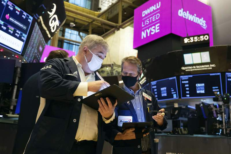 In this photo provided by the New York Stock Exchange, traders Edward McCarthy, left, and Robert Charmak work on the floor during the Delwinds Insurance Acquisition Corp. IPO, Friday Dec. 11, 2020. U.S. stocks fell in morning trading Friday as prospects for another aid package from Washington faded while a surge in virus cases threatens to inflict more damage on an already battered economy. (Colin Ziemer/New York Stock Exchange via AP)