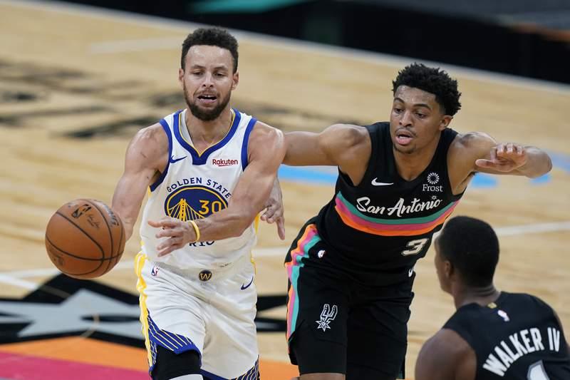 Golden State Warriors guard Stephen Curry (30) drives past San Antonio Spurs forward Keldon Johnson (3) during the second half of an NBA basketball game in San Antonio, Tuesday, Feb. 9, 2021. (AP Photo/Eric Gay)