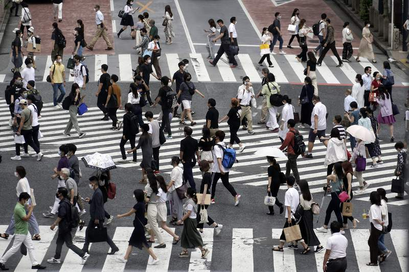 FILE - In this July 31, 2020, file photo, people wearing face masks against the spread of the coronavirus walk at Shibuya pedestrian crossings in Tokyo. Japans exports plunged 19.2% in July from a year earlier, as the coronavirus pandemic sapped global demand for goods from the third largest economy, government data showed Wednesday, Aug. 19, 2020. (AP Photo/Eugene Hoshiko, File)