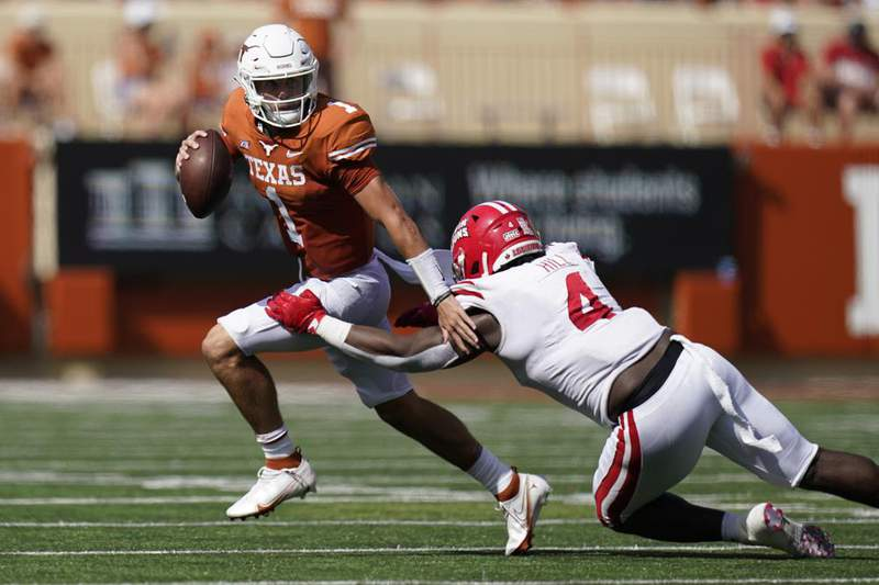 Texas quarterback Hudson Card (1) is pressured by Louisiana-Lafayette defensive lineman Zi'Yon Hill (4) during the first half of an NCAA college football game, Saturday, Sept. 4, 2021, in Austin, Texas.