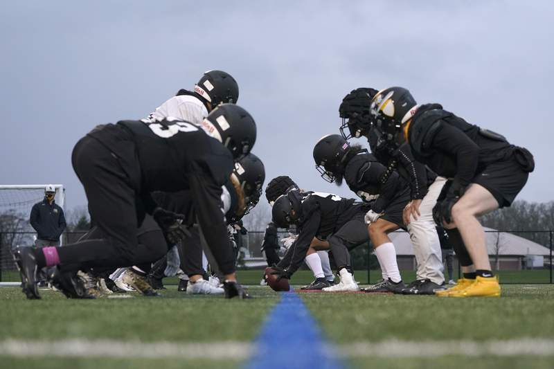 FILE- In this Tuesday, Feb. 2, 2021, file photo, university football players wait for the snap on the line of scrimmage during practice in Tacoma, Wash. Heart inflammation is rare in Big Ten Conference athletes whove had COVID-19 and in most cases causes no obvious symptoms, according to the first data published from the Big Ten COVID-19 Cardiac Registry on Thursday, May 27, 2021, in JAMA Cardiology. (AP Photo/Ted S. Warren, File)
