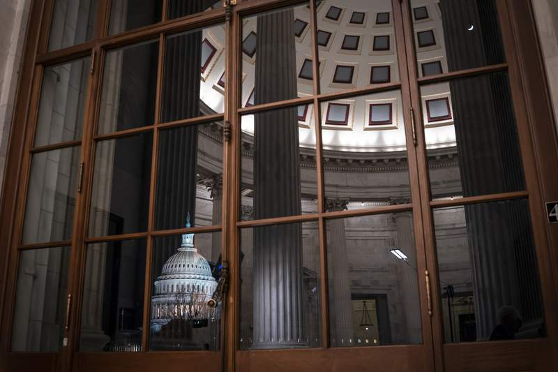 FILE - In this Jan. 29, 2020, file photo the Capitol is seen amid reflections of the Russell Senate Office Building in Washington. On Wednesday, Feb. 12, the Treasury Department releases federal budget data for January. (AP Photo/J. Scott Applewhite, File)