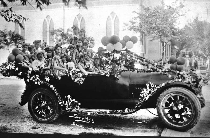 Olive Ayres, former president of the Battle of Flowers Association, poses in her entry for the Parade. Her car is decorated with pond lilies and clusters of balloons. Photo taken April 20, 1917.