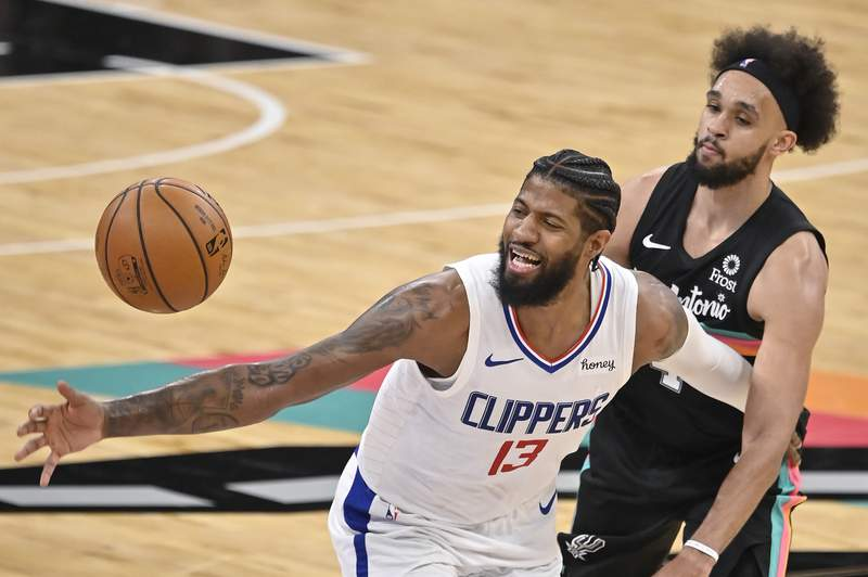 Los Angeles Clippers' Paul George (13) loses the ball as he is fouled by San Antonio Spurs' Derrick White during the second half of an NBA basketball game on Thursday, March 25, 2021, in San Antonio. (AP Photo/Darren Abate)