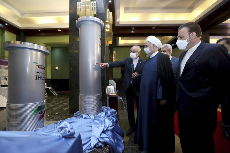 FILE - In this April 10, 2021, file photo released by the official website of the office of the Iranian presidency, Iranian President Hassan Rouhani, second from right, listens to the head of the Atomic Energy Organization of Iran Ali Akbar Salehi while visiting an exhibition of Iran's new nuclear achievements in Tehran, Iran. Iran's nuclear program has been targeted by diplomatic efforts and sabotage attacks over the last decade, with the latest incident striking its underground Natanz facility. The attack Sunday, April 11, 2021 at Natanz comes as world powers try to negotiate a return by Iran and the U.S. to Tehran's atomic accord. (Iranian Presidency Office via AP, File)