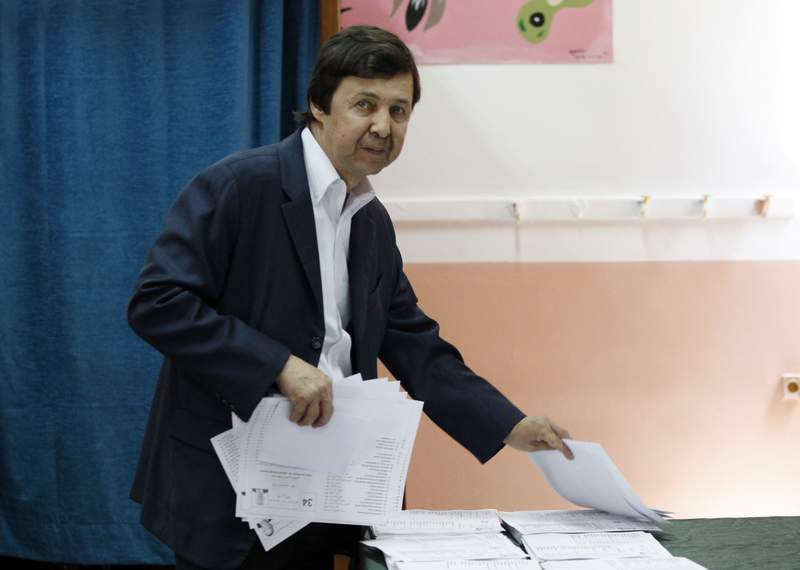 FILE - In this Thursday, May 4, 2017 file photo, Said Bouteflika, the brother of Algerian President Abdelaziz Bouteflika, takes ballots before voting in Algiers. A military appeal court in Algeria on Saturday has cleared the brother of the country's longtime former leader, two ex-intelligence chiefs and the leader of a leftist political party who had all been accused of plotting against the state. (AP Photo/Sidali Djarboub, File)
