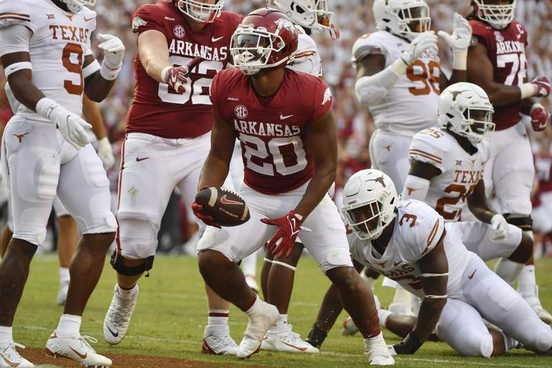 Arkansas running back Dominique Johnson (20) celebrates after scoring a touchdown against Texas during the first half of an NCAA college football game Saturday, Sept. 11, 2021, in Fayetteville, Ark.