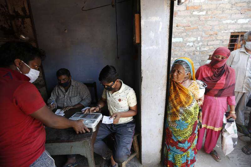 An Impoverished Indians gives his finger print on a biometric machine after purchasing food ration in Prayagraj, India, Thursday, April 2, 2020. India is adding more resources to tackle its increase in coronavirus cases by announcing that private hospitals may be requisitioned to help treat virus patients, and turning railway cars and a motor racing circuit into makeshift quarantine facilities. The steps were taken after a nationwide lockdown announced last week by Prime Minister Narendra Modi led to a mass exodus of migrant workers from cities to their villages, often on foot and without food and water, raising fears that the virus may have reached to the countryside, where health care facilities are limited. (AP Photo/Rajesh Kumar Singh)