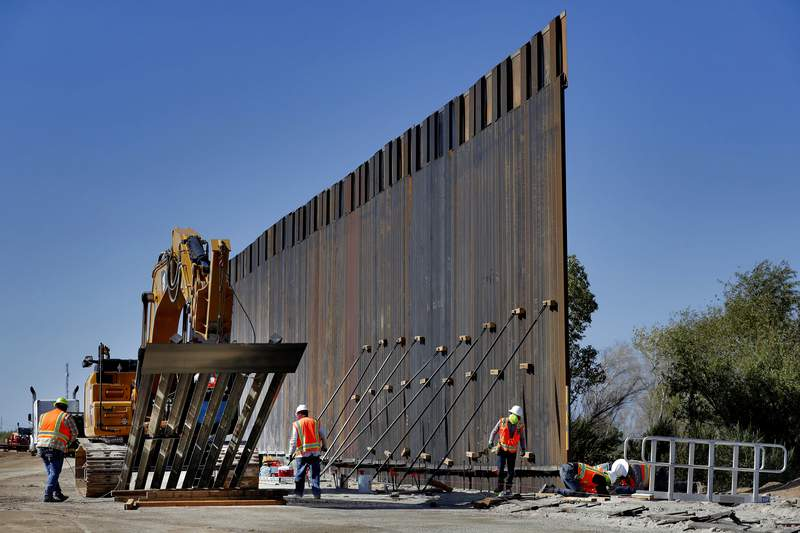 FILE - In this Sept. 10, 2019 file photo, government contractors erect a section of Pentagon-funded border wall along the Colorado River in Yuma, Ariz. The White House says construction of the U.S.-Mexico border wall will move forward after a federal appeals court ruling that frees up construction money.