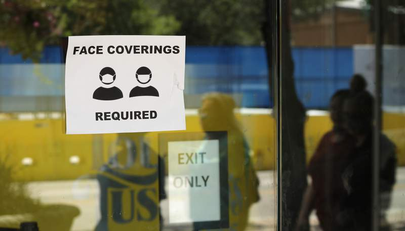 FILE - People wearing masks to protect against the spread of COVID-19 are reflected next to a sign requiring face coverings at a business in San Antonio, Wednesday, June 24, 2020, in San Antonio. (AP Photo/Eric Gay)