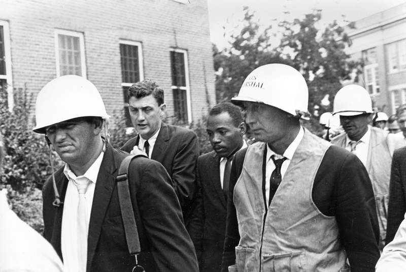 FILE- In this Oct. 1, 1962, file photo, James Meredith, center, is escorted by federal marshals as he appears for his first day of class at the previously all-white University of Mississippi, in Oxford, Miss.(AP Photo, File)