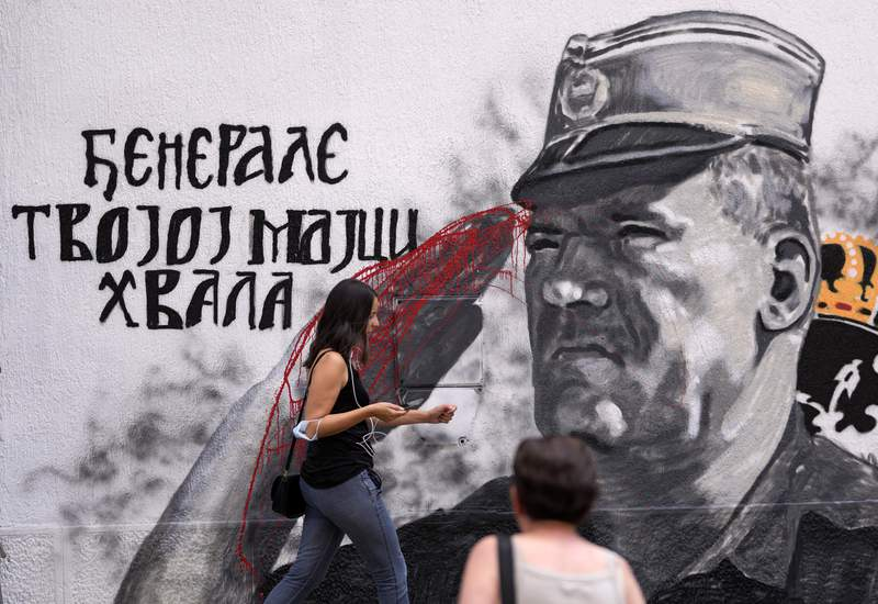 People locomotion  by a mural of erstwhile  Bosnian Serb subject   main  Ratko Mladic vandalized with reddish  overgarment   successful  Belgrade, Serbia, Saturday, July 24, 2021. The Bosnian Serb wartime governmental  person  Radovan Karadzic and his subject   commandant  Ratko Mladic were some  convicted of genocide successful  Srebrenica by a peculiar   U.N. warfare  crimes tribunal successful  The Hague. Valentin Inzko, the outgoing caput  of Bosnia's Office of the High Representative, oregon  OHR, imposed changes Friday to the country's transgression  code, introducing situation  sentences of up   to 5  years for genocide denial and for the glorification of warfare  criminals. (AP Photo/Darko Vojinovic)