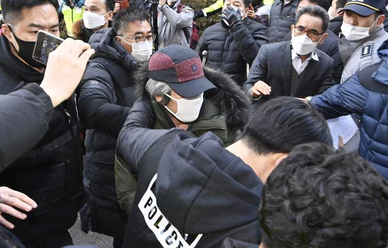 Cho Doo-soon, center, escorted by police officers, arrives home in Ansan, South Korea, Saturday, Dec. 12, 2020. Angry protesters threw eggs and shouted insults as Cho, one of South Koreas most notorious child predators, was released from a prison in southern Seoul on Saturday at the end of a 12-year term. (Kim Jong-taek/Newsis via AP)