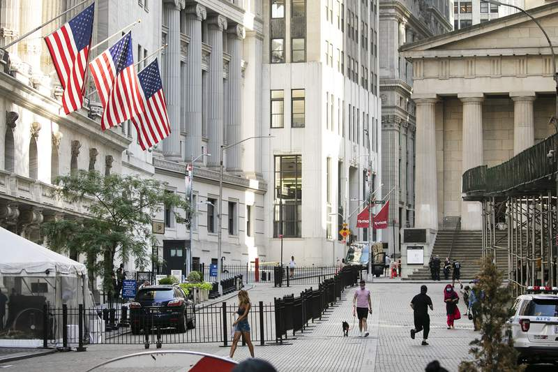 FILE - People walk by the New York Stock Exchange, left, Tuesday, July 21, 2020.  Stocks are drifting again on Wall Street Friday, Aug. 21, following a mixed set of data on the economy, as a record-breaking but wishy-washy week of trading closes out.    (AP Photo/Mark Lennihan)