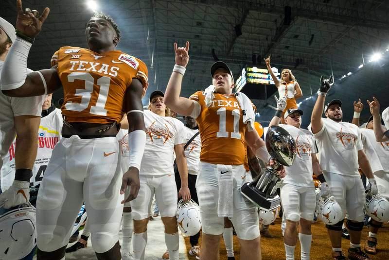 The University of Texas football team celebrates after defeating the Utah Utes at the Valero Alamo Bowl at the Alamodome in San Antonio.