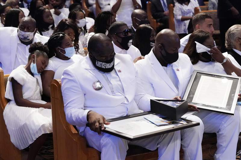 The family of George Floyd handles items given to them by Houston Mayor Sylvester Turner during the funeral service for George Floyd at The Fountain of Praise church Tuesday, June 9, 2020, in Houston. (AP Photo/David J. Phillip, Pool)