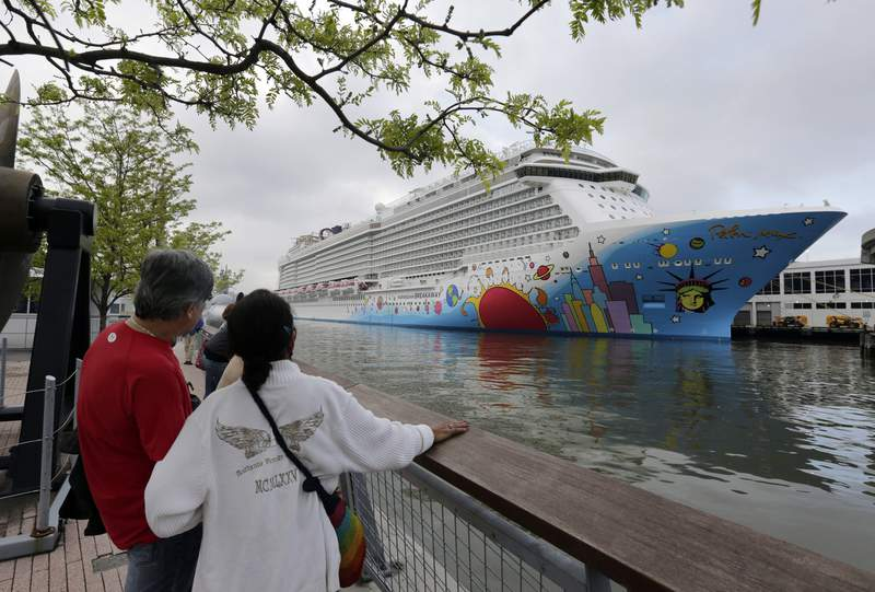 FILE - In this May 8, 2013, file photo, people pause to look at Norwegian Cruise Line's ship, Norwegian Breakaway, on the Hudson River, in New York. On Monday, April 5, 2021, Norwegian Cruise Lines parent company asked the Centers for Disease Control and Prevention for permission to resume cruises from U.S. ports on July 4 by requiring passengers and crew members to be vaccinated against COVID-19 at least two weeks before the trip. (AP Photo/Richard Drew, File)