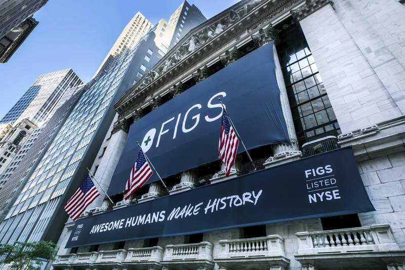 This photo provided by the New York Stock Exchange, a banner for Figs hangs on the New York Stock Exchange, Thursday, May 27, 2021.  Shares of online scrubs seller Figs are soaring in their stock market debut, valuing the 8-year old company at $4.8 billion. Founded in 2013, Figs set out to remake what medical scrubs looked like: from boxy, V-necked and baggy to a more fitted silhouette.   (Courtney Crow/New York Stock Exchange via AP)