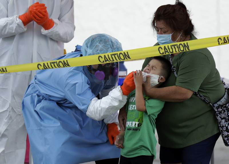 FILE - In this May 14, 2020, file photo, Jerry A Mann, center, is held by his grandmother, Sylvia Rubio, as he is tested for COVID-19 by the San Antonio Fire Department at a free walk-up test site in San Antonio. (AP Photo/Eric Gay, File)