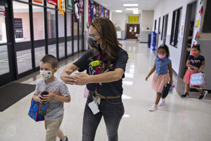 Kindergarten teacher Mrs. Hogan instructs students to make a bubble of room between other students on the first day of in-person classes at Highland Village Elementary. Credit: Shelby Tauber for The Texas Tribune