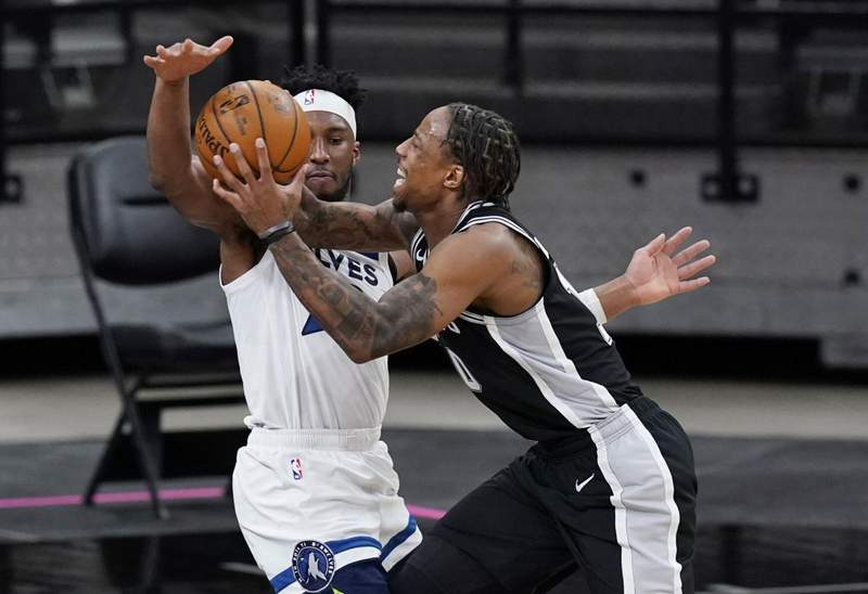 San Antonio Spurs forward DeMar DeRozan, right, drives against Minnesota Timberwolves guard Josh Okogie during the second half of an NBA basketball game in San Antonio, Wednesday, Feb. 3, 2021.