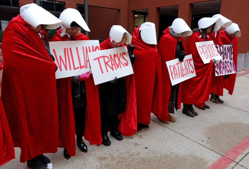 """FILE - In this Oct. 31, 2019, file photo, Planned Parenthood supporters dressed In """"The Handmaid's Tale"""" costumes stand in silence in St. Louis before the fourth day of hearings between Planned Parenthood and Missouri Department of Health and Senior Services. Government funding for Missouri Planned Parenthood clinics is at stake in a lawsuit set to be argued before the state Supreme Court on Tuesday, Dec. 10. (Laurie Skrivan/St. Louis Post-Dispatch via AP, File)"""