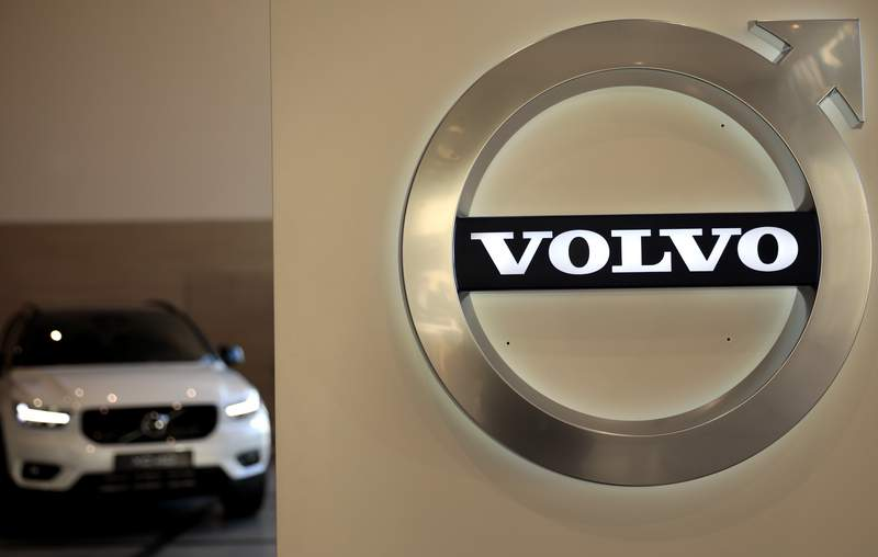 FILE - In this Feb. 6, 2020 file photo a Volvo car is parked behind the Volvo logo in the lobby of the company's corporate headquarters, in Brussels.  Volvo says it will make only electric vehicles by 2030. But for those who want one, they will have to buy it online.  The Swedish automaker said Tuesday, March 2, 2021,  that it is phasing out the production of all cars with internal combustion engines  including hybrids.  (AP Photo/Virginia Mayo, File)