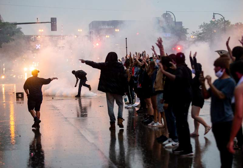 """MINNEAPOLIS, MN - MAY 26: Tear gas is fired as protesters clash with police while demonstrating against the death of George Floyd outside the 3rd Precinct Police Precinct on May 26, 2020 in Minneapolis, Minnesota. Four Minneapolis police officers have been fired after a video taken by a bystander was posted on social media showing Floyd's neck being pinned to the ground by an officer as he repeatedly said, """"I can't breathe"""". Floyd was later pronounced dead while in police custody after being transported to Hennepin County Medical Center. (Photo by Stephen Maturen/Getty Images)"""