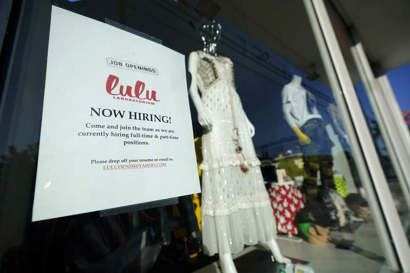 """A """"Now Hiring"""" sign is shown in the window of a store, Wednesday, Jan. 27, 2021, in the Wynwood Arts District of Miami. The number of Americans applying for unemployment benefits fell to a historically high 847,000 last week, a sign that layoffs remain high as the coronavirus pandemic continues to rage. (AP Photo/Wilfredo Lee)"""