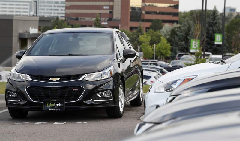 FILE - In this June 26, 2018, file photograph, a used 2017 Chevrolet Cruze sits in a row of other used, late-model sedans at a dealership in Centennial, Colo. A shortage of used vehicles in the U.S. has pushed up prices, and that caused much of September 2020's modest inflation increase. (AP Photo/David Zalubowski, File)