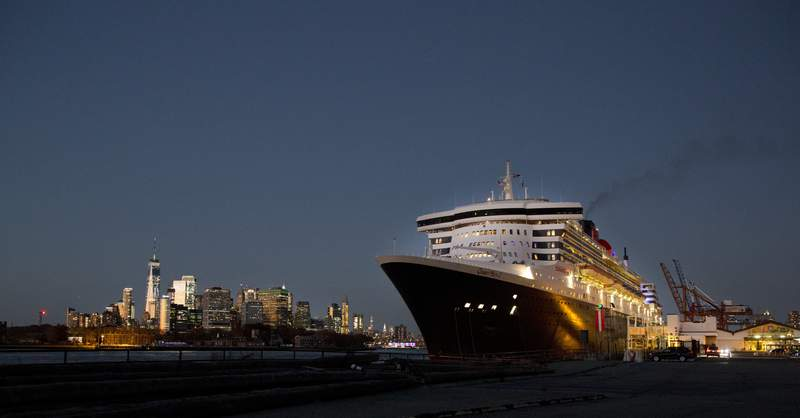 FILE - In this Sunday, Nov. 11, 2018, file photo, the Queen Mary 2 prepares to depart the Red Hook Terminal, bound for Southampton, England, in the Brooklyn borough of New York. The Manhattan skyline is at left. Cunard Line is pushing back the return of the Queen Mary 2, which has already been idled for 18 months because of the pandemic. Cunard said Thursday, Sept. 2, 2021, it is canceling the ship's first four scheduled cruises, which included two trips across the Atlantic. (AP Photo/Mark Lennihan, File)