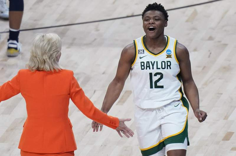 Baylor guard Moon Ursin (12) and head coach Kim Mulkey celebrate the team's overtime win over Michigan in a college basketball game in the Sweet Sixteen round of the women's NCAA tournament at the Alamodome in San Antonio, Saturday, March 27, 2021.