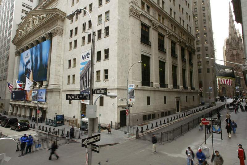 People make their way along Wall Street in front of the New York Stock Exchange building Friday, Oct. 29, 2004, on the 75th anniversary of the 1929 stock market crash. The stock market  in  1929 drove the Dow Jones industrials down 23.9 percent, sparking a widespread panic that helped sink the nation into the Great Depression.  (AP Photo/Gregory Bull)