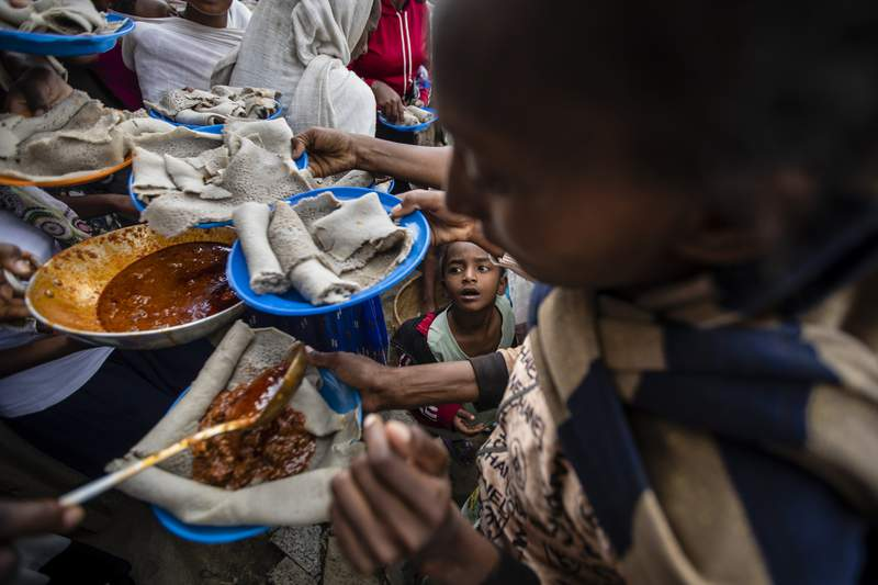 A young boy looks up as displaced Tigrayans line up to receive food donated by local residents at a reception center for the internally displaced in Mekele, in the Tigray region of northern Ethiopia, on Sunday, May 9, 2021. The 15 kilograms of wheat, half a kilogram of peas and some cooking oil per person, to last a month  was earmarked only for the most vulnerable. That included pregnant mothers and elderly people. (AP Photo/Ben Curtis)