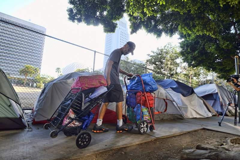 FILE - In this July 1, 2019 file photo, a homeless man moves his belongings from a street near Los Angeles City Hall, background, as crews prepared to clean the area. Los Angeles city and county officials on Tuesday, Feb.18, 2020 announced a new strategy to speed the process of getting homeless people into permanent housing that is modeled on the federal government's response to natural disasters. (AP Photo/Richard Vogel, File)