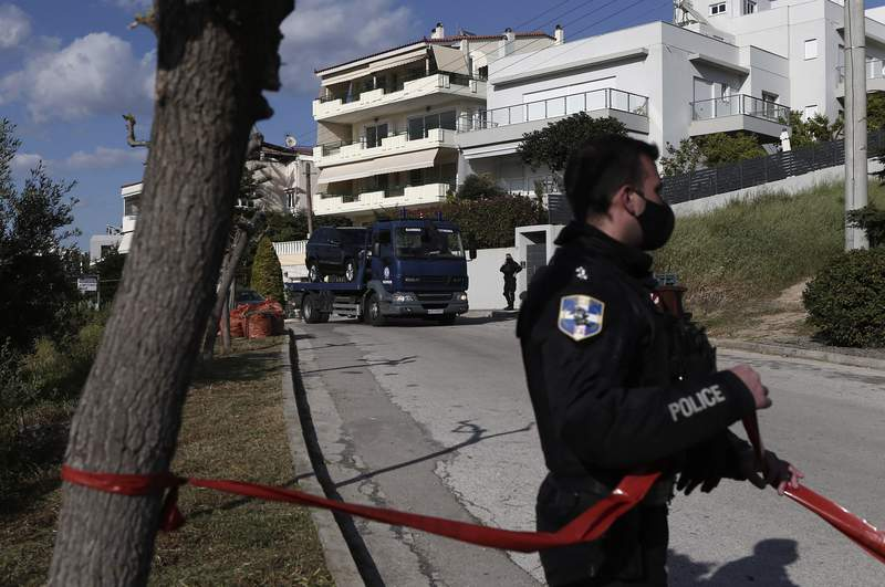 A police truck carries the car of a veteran Greek crime reporter in southern Athens, Friday, April 9, 2021. Giorgos Karaivaz was gunned down Friday near his home in southern Athens, police said. Private Star TV, for which he worked, said Karaivaz had just returned from work. It said two men on a motorcycle drew up beside him and the passenger opened fire. (Panayiotis Tzamaros/InTime News via AP)