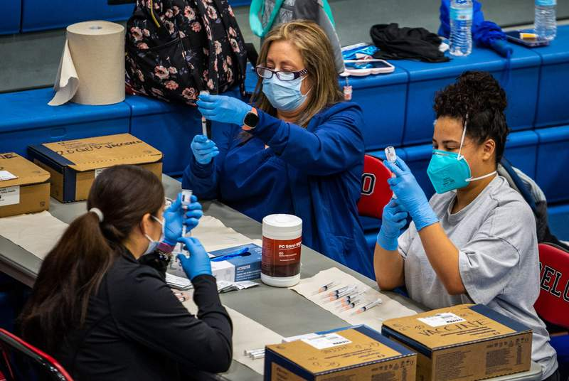 Medical workers load up syringes with vaccines for COVID-19 at the Delco Activity Center in Northeast Austin, on March 13, 2021. The center averages somewhere between 3,000 and 4,000 vaccinations daily.