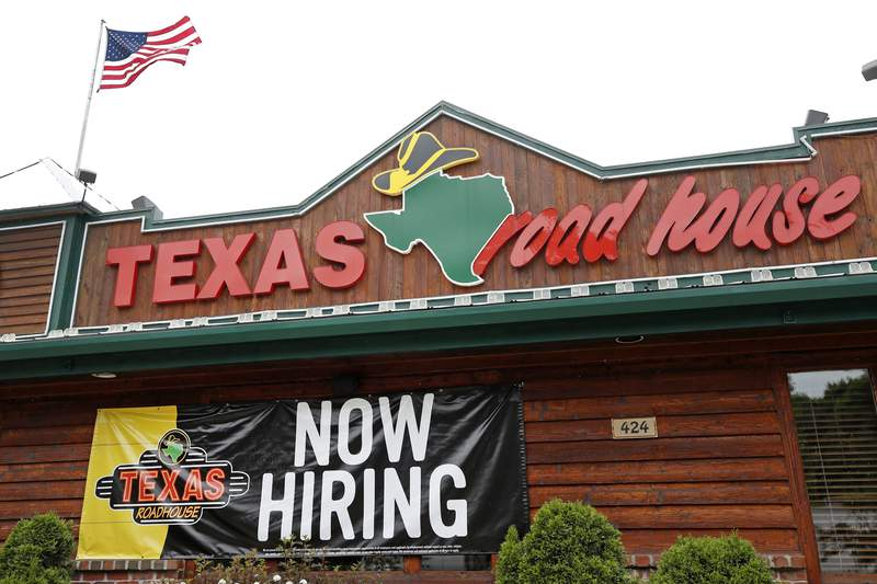 """A """"Now Hiring"""" sign Is displayed outside a Texas Roadhouse restaurant, Friday, June 5, 2020, in Methuen, Mass.  The U.S. unemployment rate fell to 13.3% in May, and 2.5 million jobs were added — a surprisingly positive reading in the midst of a recession that has paralyzed the economy and depressed the job market in the wake of the viral pandemic.  (AP Photo/Elise Amendola)"""