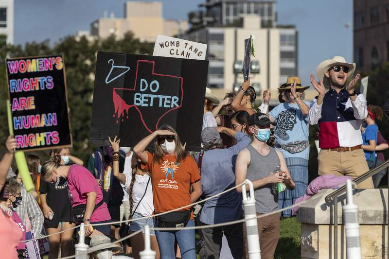 FILE - In this Oct. 2, 2021 file photo, people attend the Women's March ATX rally, at the Texas State Capitol in Austin, Texas. A federal judge has ordered Texas to suspend a new law that has banned most abortions in the state since September. The order Wednesday, Oct. 6, by U.S. District Judge Robert Pitman freezes for now the strict abortion law known as Senate Bill 8. (AP Photo/Stephen Spillman, File)