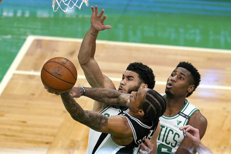 San Antonio Spurs forward DeMar DeRozan (10) drives to the basket against the defense of Boston Celtics forwards Jayson Tatum, left, and Aaron Nesmith during the first half of an NBA basketball game Friday, April 30, 2021, in Boston.