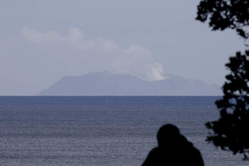 FILE  - In this Dec. 10, 2019, file photo, a man watches as a plume of steam is seen above White Island early morning off the coast of Whakatane, New Zealand. A man who died in an Australian hospital had become the 20th casualty of the New Zealand volcano eruption more than a month ago, officials said on Monday, Jan. 13, 2020. (AP Photo/Mark Baker, File)