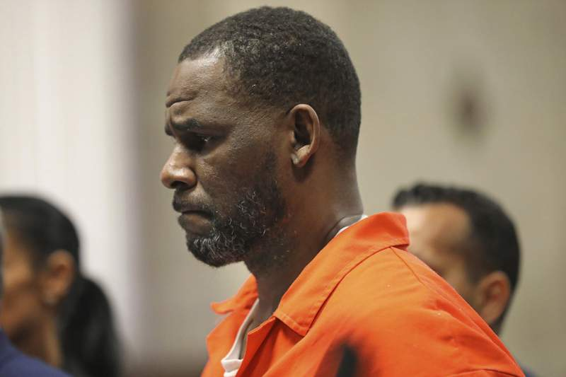 """FILE - In this Sept. 17, 2019, file photo, R. Kelly appears during a hearing at the Leighton Criminal Courthouse in Chicago. A federal judge denied Kelly's request that he be released from custody out of concern that he might contract the coronavirus. He is being held in a federal  in Chicago as he awaits trial on child pornography and other charges.  The defendant is currently in custody because of the risks that he will flee or attempt to obstruct, threaten or intimidate prospective witnesses,  U.S. District Judge Ann Donnelly of Brooklyn wrote in her denial. """"The defendant has not explained how those risks have changed. (Antonio Perez/Chicago Tribune via AP, Pool, File)"""