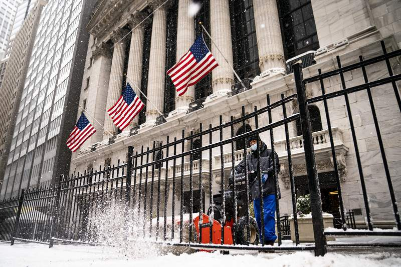A worker clears snow from the front of the New York Stock Exchange in the Financial District, Thursday, Feb. 18, 2021, in the Manhattan borough of New York. (AP Photo/John Minchillo)