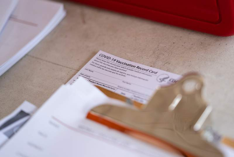 A COVID-19 Vaccination Record Card sits on a table at a vaccine clinic held in partnership between the Central Texas Food Bank and University of Texas in Austin on July 21, 2021.