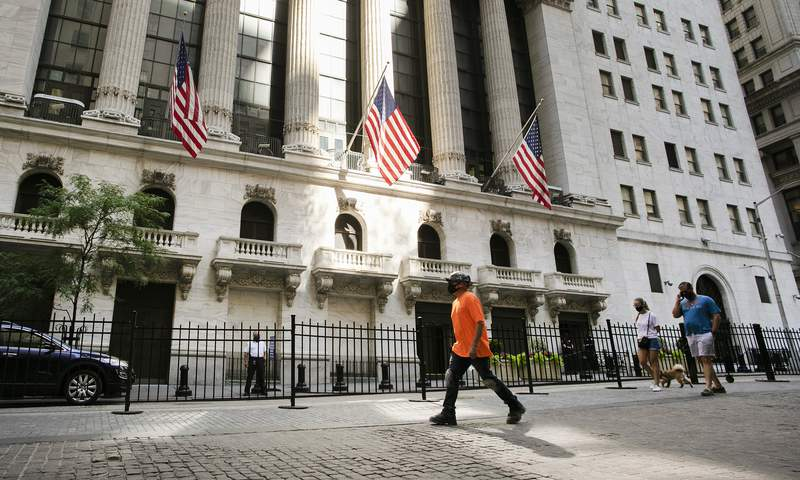FILE - In this July 21, 2020 file photo, people walk by the New York Stock Exchange.  Stocks are drifting in early Friday, Aug. 14, trading on Wall Street after a report showed that sales for U.S retailers strengthened again last month, but by less than economists expected. (AP Photo/Mark Lennihan, File)