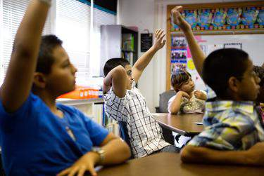 Science students at Bayless Elementary in Lubbock, raise their hands to answer a question. (Jerod Foster for the Texas Tribune)