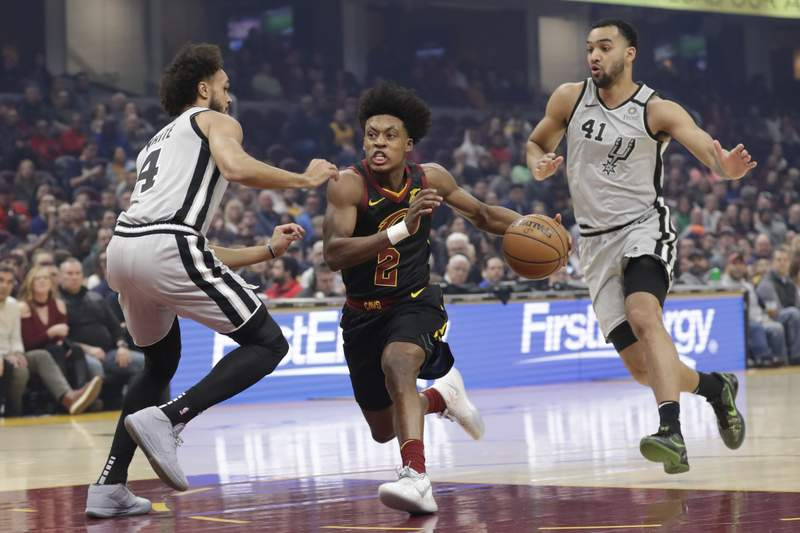 Cleveland Cavaliers' Collin Sexton (2) drivetrains vas past San Antonio Spurs' Derrick White (4) in the first half of an NBA basketball game, Sunday, March 8, 2020, in Cleveland. Trey Lyles (41) follows behind. (AP Photo/Tony Dejak)